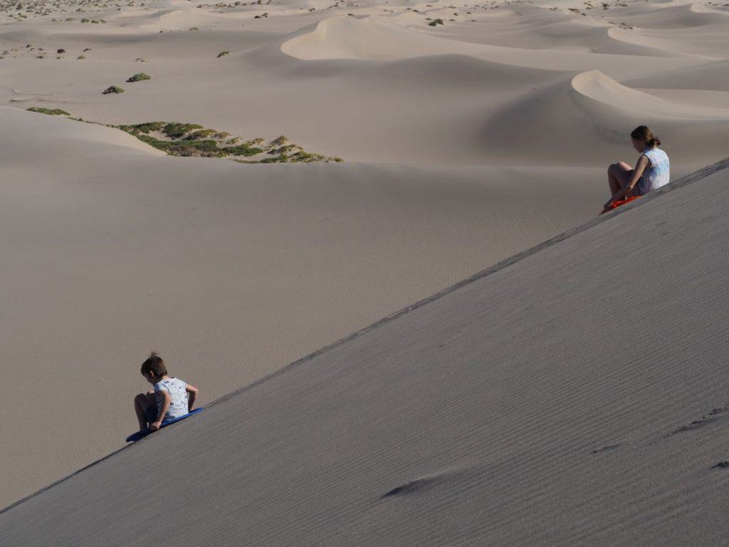 Sand boarding on the Mesquite Sand Dunes, Death Valley