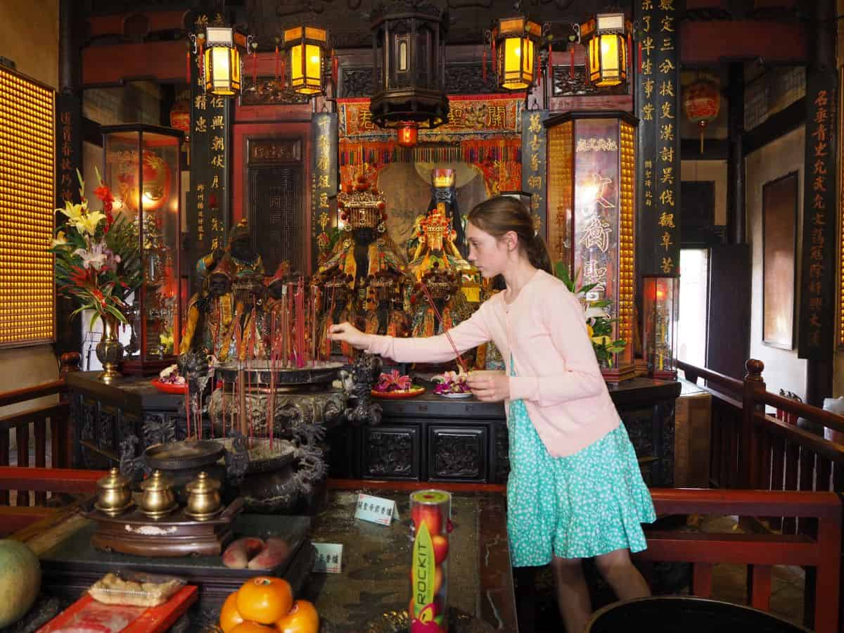 Amelie making an offering to the gods in a Taoist Temple in Tainan