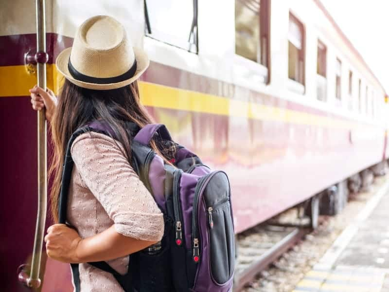girl with backpack boarding train
