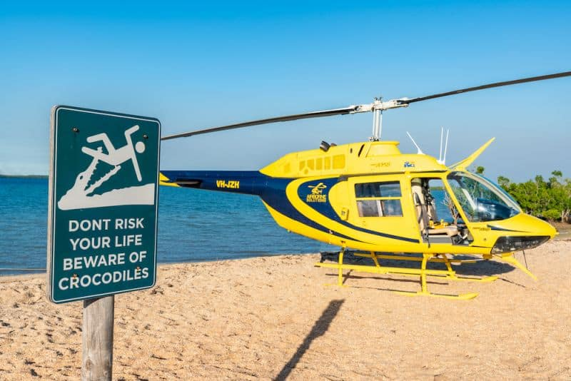 Yellow helicopter on beach in Darwin for Heli Pub Tour